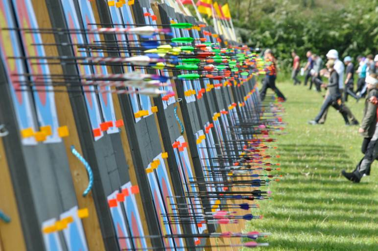 An Oxford Archers tournament with many targets bristling with arrows as archers approach to score